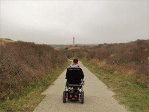 Wheelymum fährt mit dem Elektro-Rollstuhl hinter dem Deich