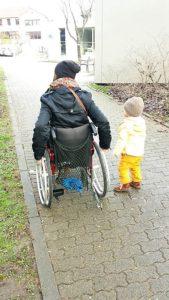 Wheelymum im Rollstuhl mit ihrem Kind daneben