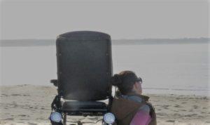 Wheelymum sitzt neben ihrem Rollstuhl am Strand